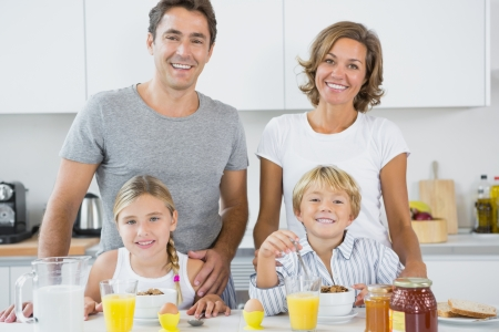 Happy family at breakfast in kitchen photo