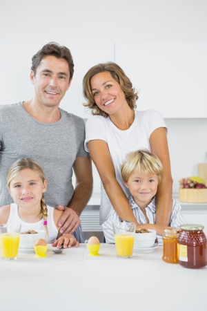 honey blonde: Smiling family at breakfast in the kitchen