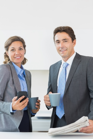 Business couple having coffee together before work in kitchen photo