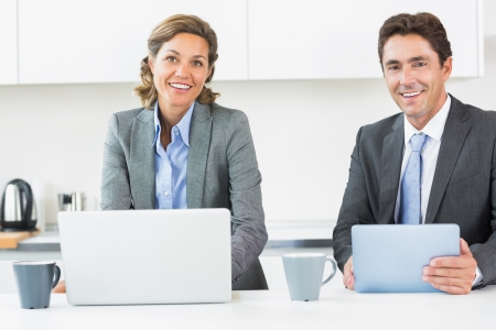 Happy couple with tablet and laptop in kitchen before work Stock Photo - 18111230