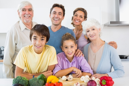 multi family house: All the family smiling in kitchen in front of chopping board with vegetables Stock Photo
