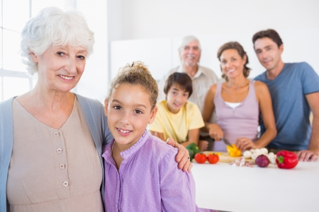 Grandmother and granddaughter standing beside counter with family behind them photo