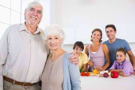 Grandparents standing by kitchen counter with family behind them photo