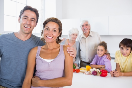 kitchen counter: Mother and father standing by kitchen counter with family behind them