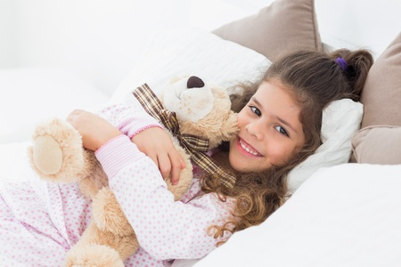 Little girl and her teddy bear on bed photo
