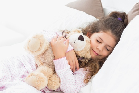 Little girl asleep with her teddy bear in bed photo