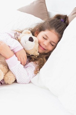 Little girl asleep with teddy in bed photo