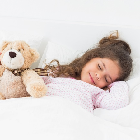 Little girl in bed sleeping with teddy bear photo