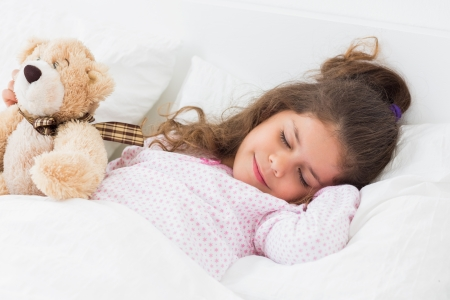 Cute girl asleep with teddy bear in bed photo