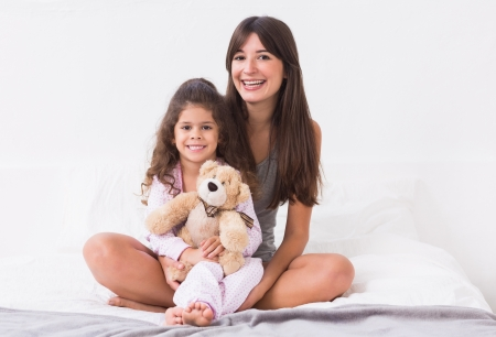 Mother and daughter sitting on bed with teddy bear in bedroom photo