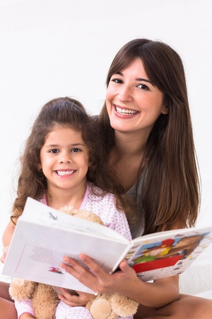 storybook: Mother and daughter reading a storybook on bed