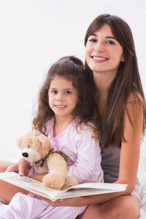 Mother and daughter reading together with teddy bear in bed photo