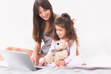 Happy mother and daughter using the laptop in bed photo