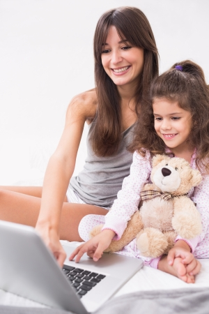 Mother and daughter using laptop with teddy bear in bed photo