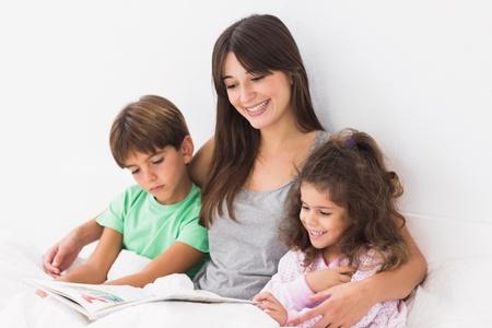 madre e hijo: Madre con sus ni�os leyendo un libro de cuentos en la cama Foto de archivo