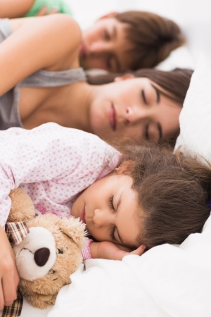 Mother and children cuddled up in bed asleep photo