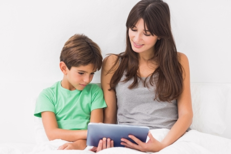 Mother and son using tablet pc in bed Stock Photo - 18115568