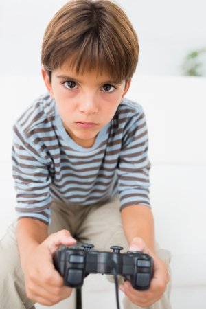 jugando videojuegos: Ni�o jugando videojuegos en el sof� Foto de archivo