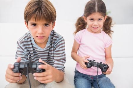 playing video games: Hermano y hermana jugando juegos de video juntos en el sof�