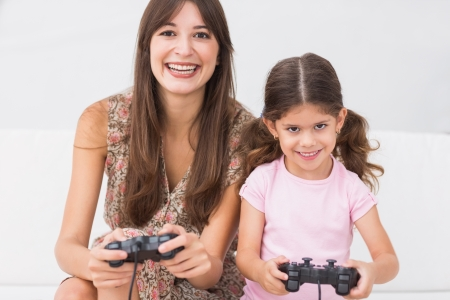 Happy mother and daughter playing video games on the couch photo