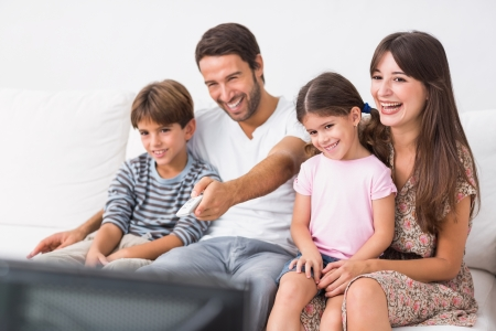 changing room: Happy family on the couch watching television together