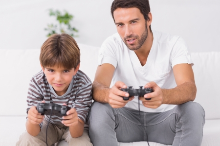 console: Father and son playing video games on the couch