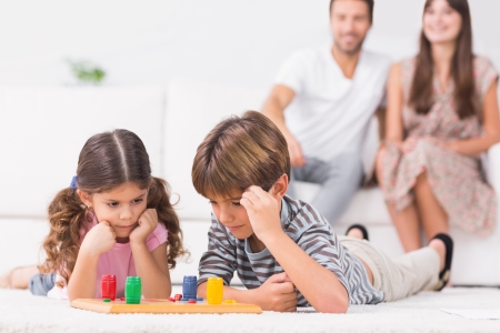 Siblings playing board game on the floor with parents sitting behind them photo
