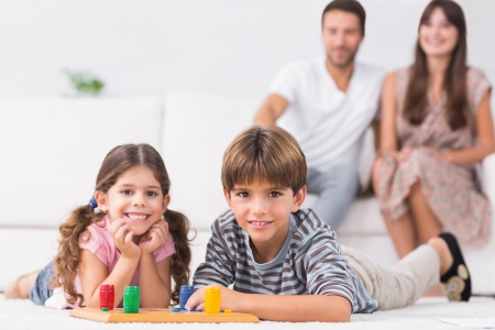 Happy siblings playing board game on floor with parents sitting behind them photo