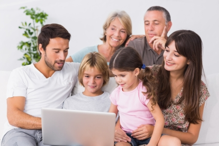 grandfather and grandmother: Happy family looking at laptop on the couch Stock Photo