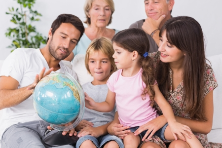 Happy family looking at globe on the couch photo