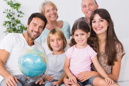 Smiling family with globe sitting on the couch photo