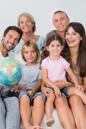 Happy family sitting on the couch with a globe Stock Photo - 18115812
