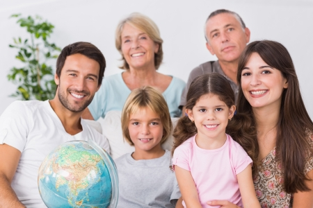 Cheerful family sitting on couch with a globe photo
