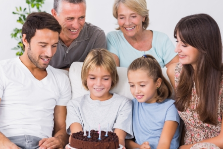 Family celebrating young boys birthday on the couch photo
