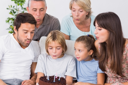 Little boy blowing out birthday candles on the couch photo