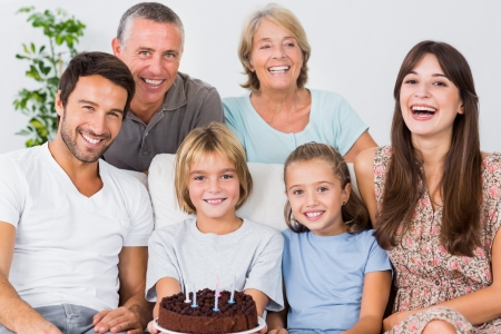 Smiling family celebrating with birthday cake photo