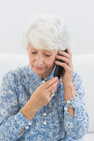 Aged woman phoning on a sofa photo