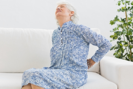 Elderly woman feeling back pain on the couch photo