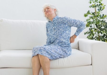Elderly woman suffering with back pain on a sofa photo