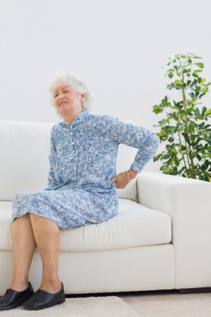 Elderly woman suffering with back pain photo