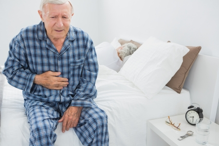 Elderly man suffering with belly pain in the bedroom photo