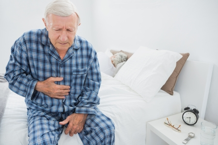 aches: Aged man suffering with belly pain