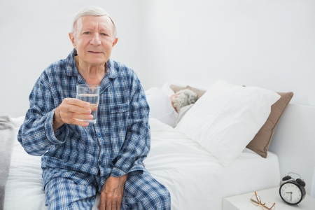 Old man with a water glass sitting on the bed photo