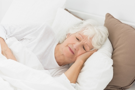Old woman sleeping on the bed photo
