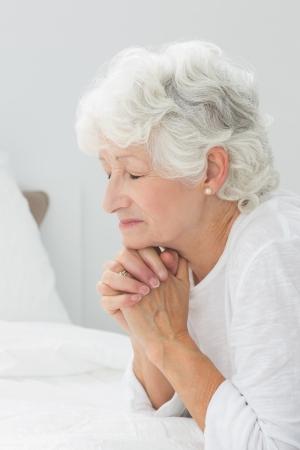 christian women: Aged woman praying before sleeping Stock Photo