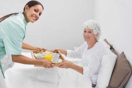 aide a domicile: Infirmi�re � domicile donnant un petit d�jeuner � la vieille femme sur le lit Banque d'images