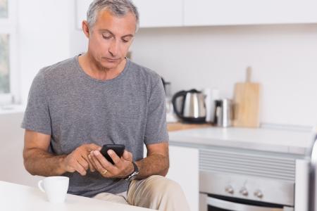 mature adult men: Uomo Focused toccando il suo smartphone in cucina
