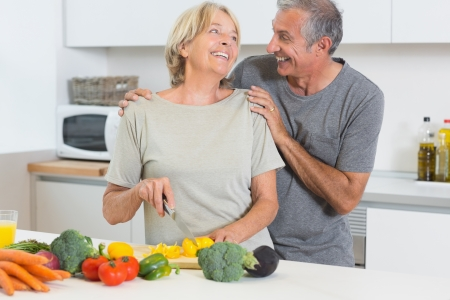 Smiling couple cutting vegetables together in the kitchen photo