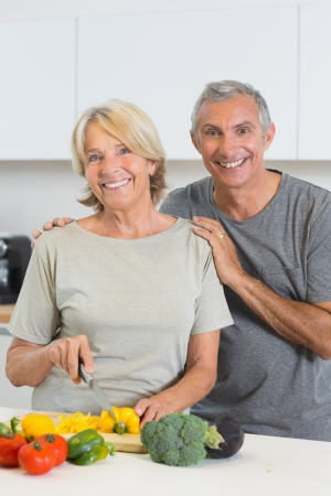 Cheerful couple cutting vegetables together in the kitchen photo