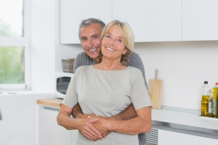 Cute mature couple hugging in the kitchen photo